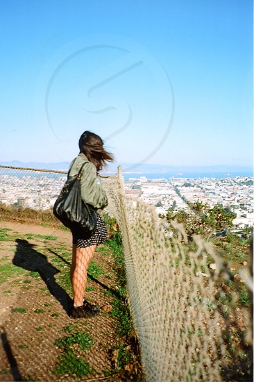 woman standing beside stainless steel fence photo