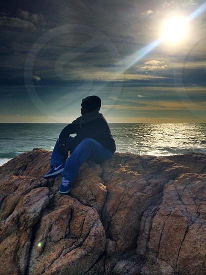 Meditation ocean solitary sun flair reflection rock mountain  photo
