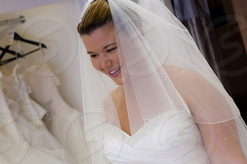 woman with brown hair wearing veil and white wedding dress photo