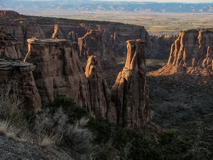 Evening shadows on the rock pinnacles and spires of Colorado National Monument USA with a view of the Colorado River beyond. Center spire is the Kissing Couple. photo