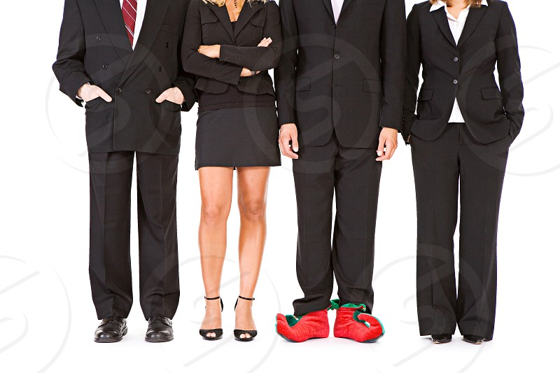 Business Team Member Wearing Elf Shoes.  Christmas holiday business team businesswoman elf shoes standing out from the crowd suit man woman unique photo