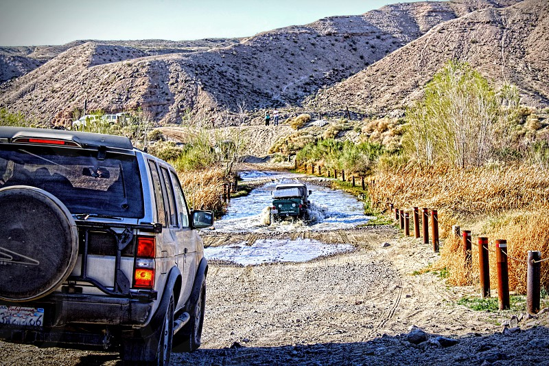 Seen from behind them two jeeps drive through water in a high desert. photo