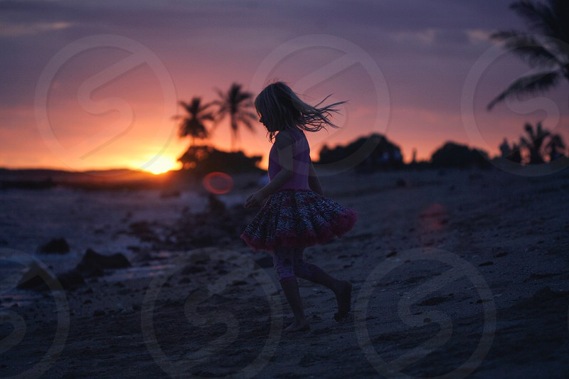 child in pink dress walking on sand photo