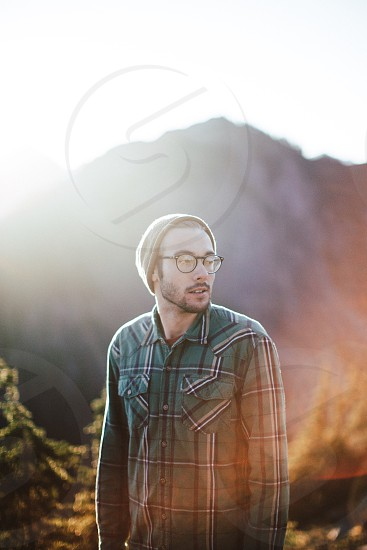smiling man in green black and white plaid dress shirt wearing gray knit cap and black framed eyeglasses looking sideways below mountain under white sunny sky photo