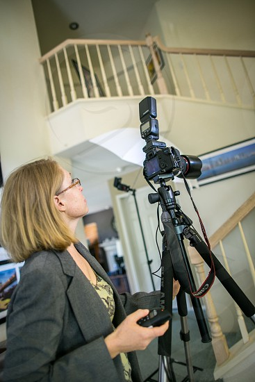 A professional photographer shoots a property. House stairs grey blazer yellow woman lady female girl tripod camera flash remote architecture structure building real estate home. photo