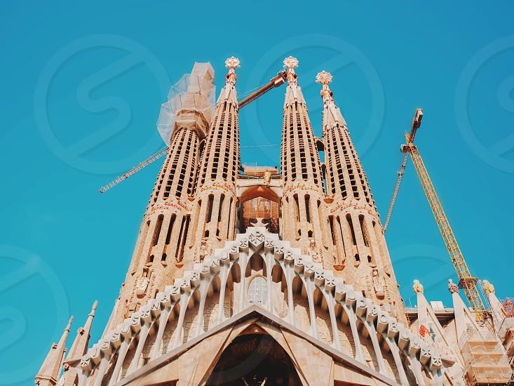 "BARCELONASPAIN-OCTOBER 32017 Frontal view of this architecture masterpiece ""La Sagrada Familia"" by Antoni Gaudi. Picture with cranes. photo"