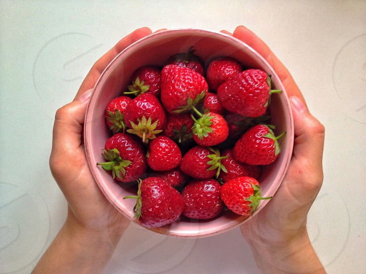 Hands holding full bowl of strawberry  photo