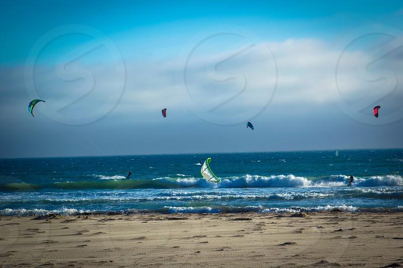Windsurfers on a bright sunny beach photo