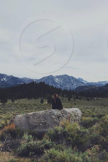 woman sitting on grey rock photo