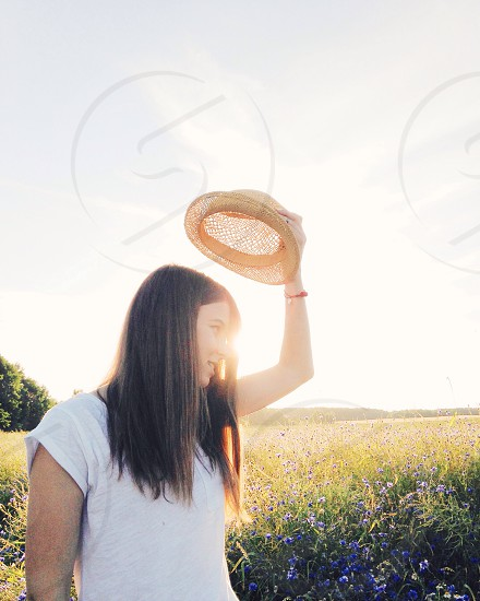 woman with hat in flower field photo