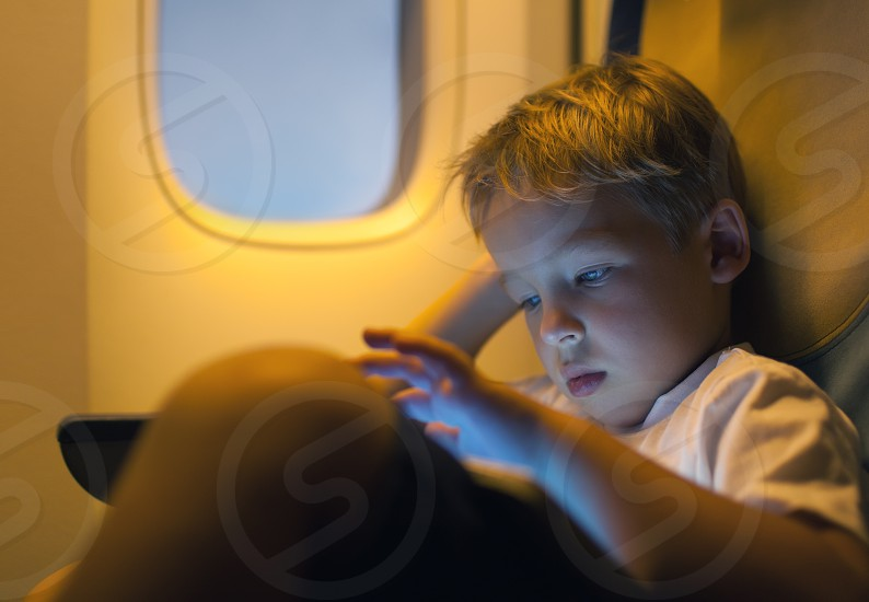 Close-up shot of a little boy playing on touch pad during in the plane. Child looking tired or bored photo
