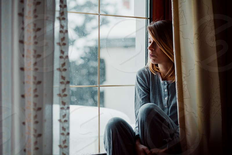 Sad woman sitting by the window looking outside photo