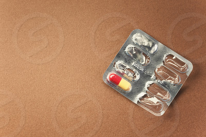 Conceptual composition empty pills pack with just one left symbolically represents last chance or simple a cure the need and similar.  photo