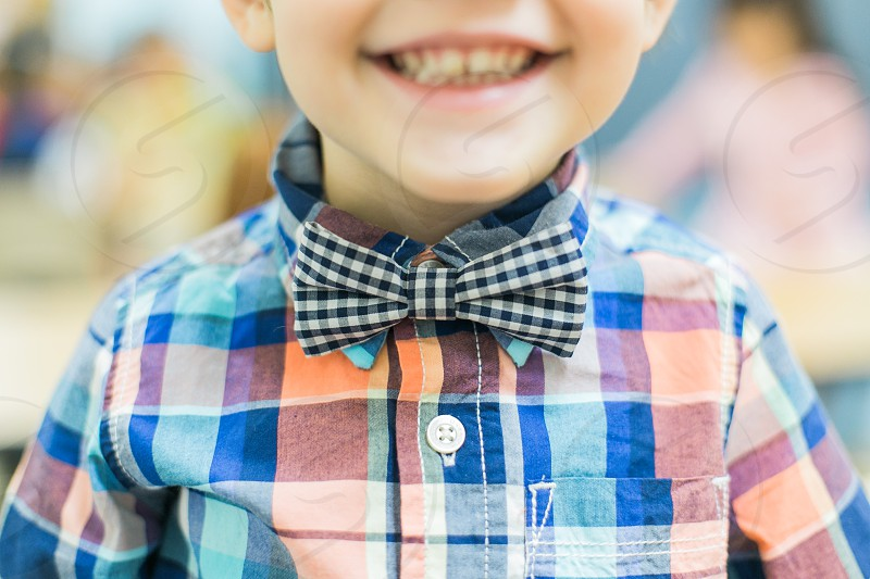 boy in blue pink checkered button up shirt with black white checkered bowtie smiling photo