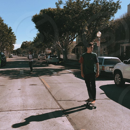 man in green and brown crew neck t shirt skate boarding on road during daytime photo