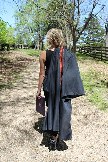 Graduate walking away with gown over her shoulder and diploma in hand. photo