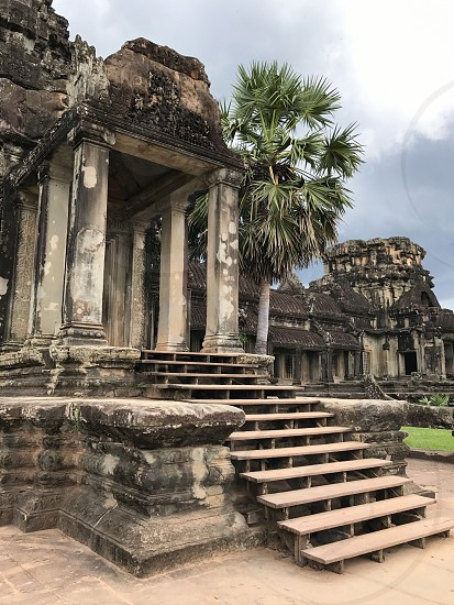 Outdoor day colour vertical portrait Angkor Wat Temple holy religious spiritual National Park Cambodia east eastern Asia Asian park nature tree palm trees sky clouds pretty travel travelling tourism tourist wanderlust adventure exploration summer natural landmark building architecture Ruins ancient stormy atmospheric photo