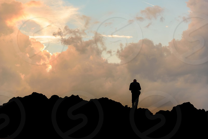 Slihouette of a man at the top of the rock with cloudy sky at sunset photo