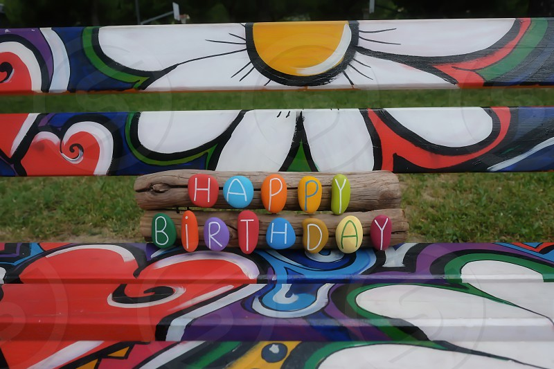 Happy Birthday text with colored stones on a creative painted public bench photo