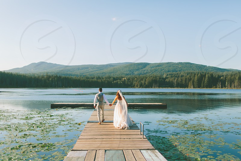 A bride and groom running down a dock at the lake.  photo