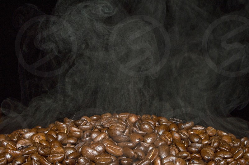 Closeup of coffee beans roasting with smoke. photo