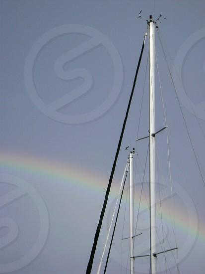 Sailboat mast with rainbow safe harbour photo