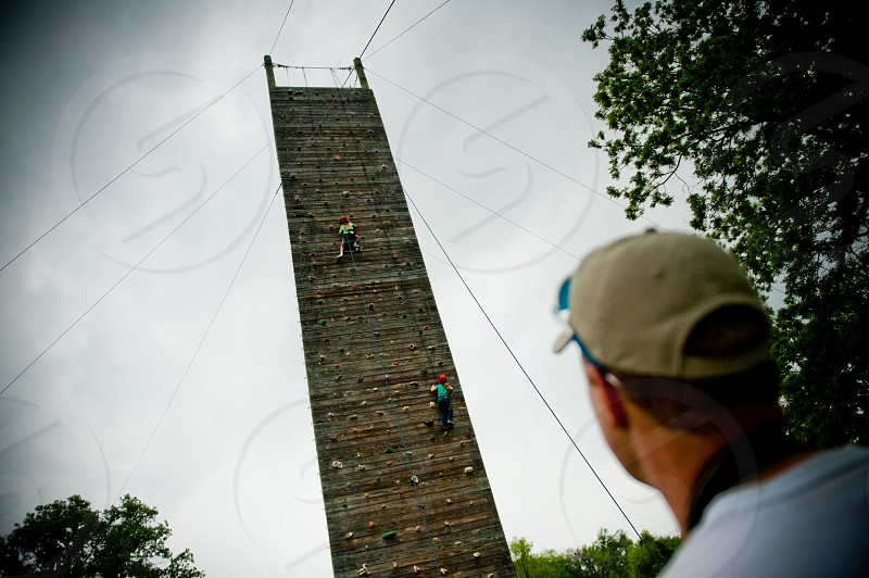 Dad watching young daughter climb very tall wall photo