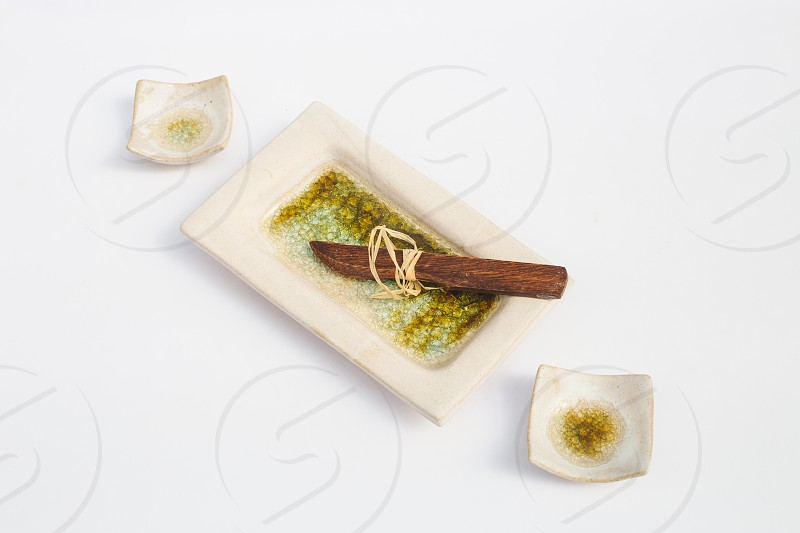 three ceramic stoneware wells and a wooden knife with white background photo