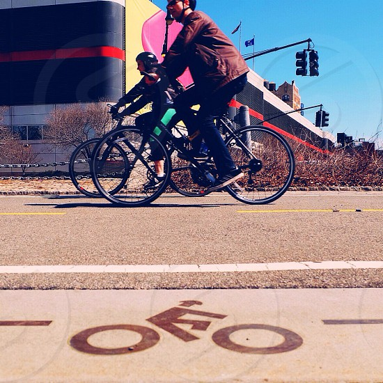 man and woman riding a mountain bike on road photo