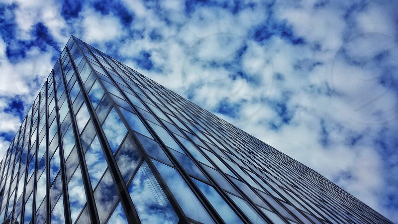 ground view looking up at a skyscraper under a cloudy sky photo