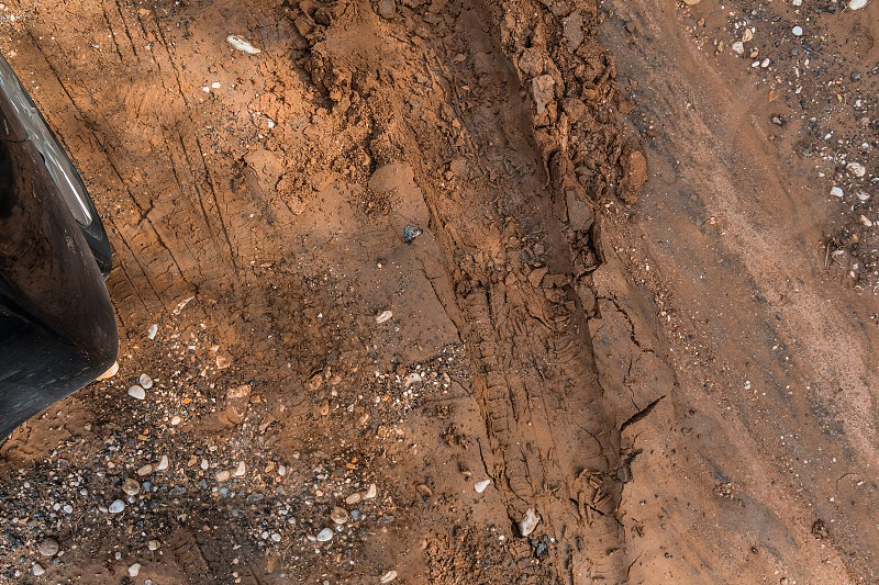 Texture of wet brown mud with car tyre tracks and shoe footprint photo