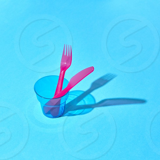 Colorful set of disposable fork and knife in a transparent glass with long shadows place for text. photo