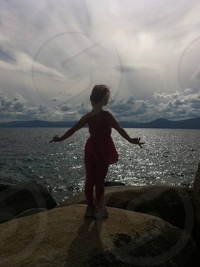 This is a picture of my sister in front of Lake Tahoe California/Nevada.  Lake tahoe cali california nevada girl water rocks travel we travel sky photo