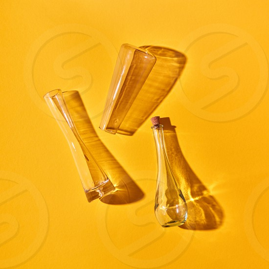 Three empty glass bottles lie on a yellow background with shadows and reflection place for text. Top view. Test glass flask in research laboratory. Science and medical background. photo