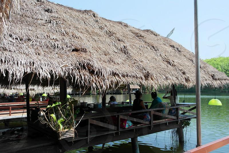 people on brown nipa hut on body of water photo
