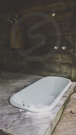 Outside bathtub on deck of rustic tree house  photo