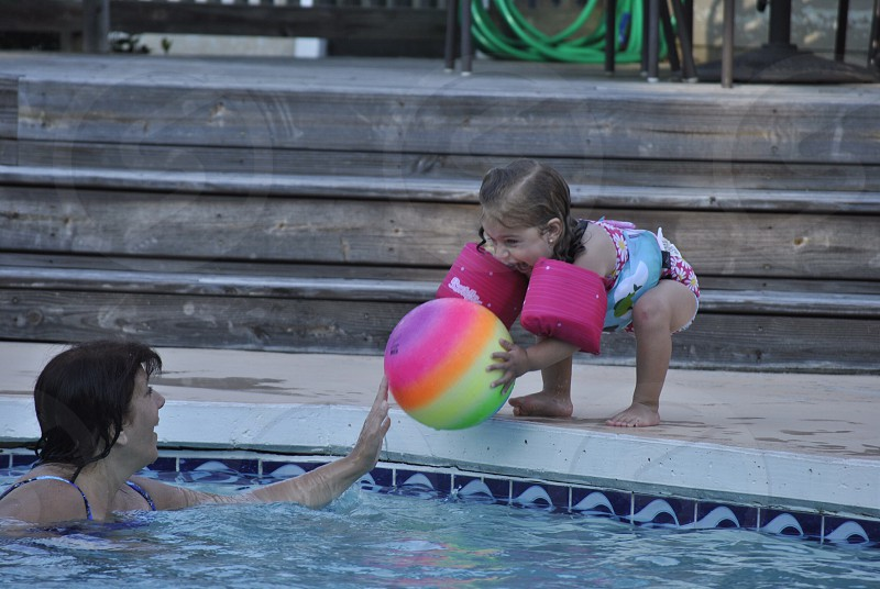 girl holding multicolored ball beside pool with woman in blue cami-strap top during daytime photo