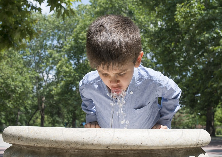 Child drinking water from a fountain. Close up photo