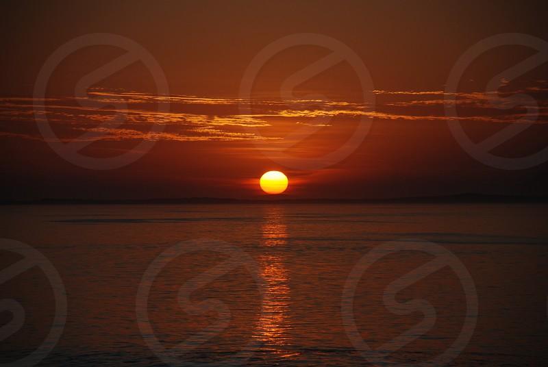 Sun sunset sunrise ocean sea orange circle clouds beach photo