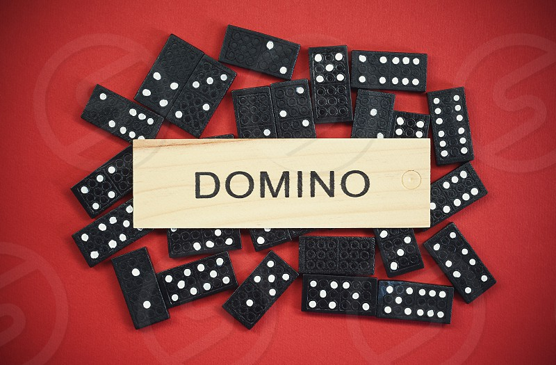 Bunch of dominoes under wooden tile with title on it on red background.  photo