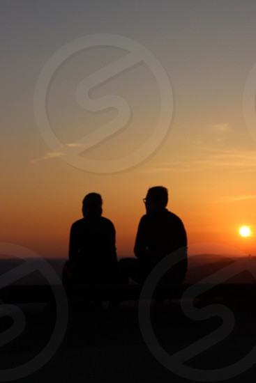 two man sitting with sunset view photo