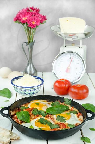 Turkish shakshuka on pan with ingredients on light background photo