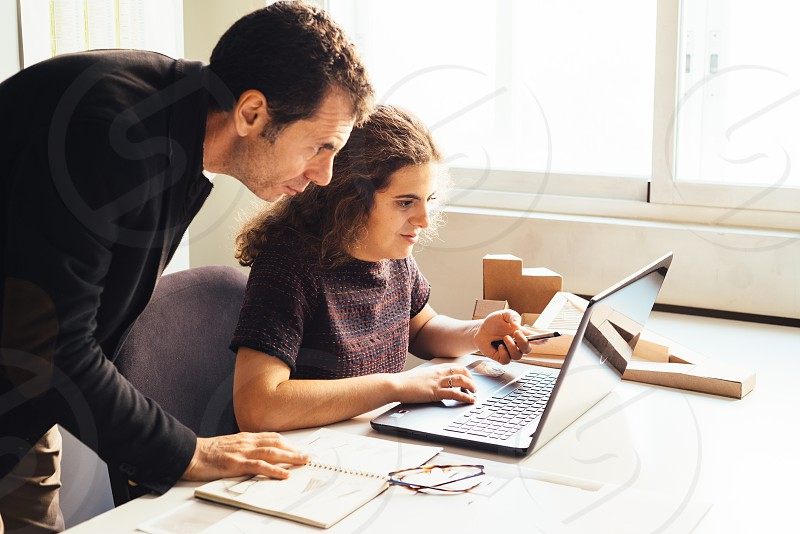 Two architects adult man and young woman working with laptop at office desk photo