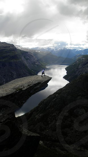 A subject at the top of an immense rock formation sticking out looking down at the ravine and the fjord. photo