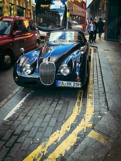 black vintage jaguar roadster parked on london street at daytime photo