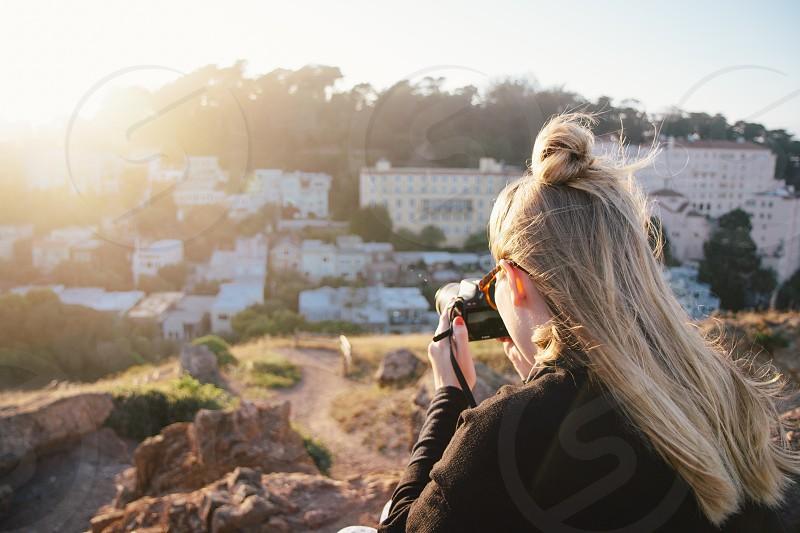 blonde woman in brown jacket taking photo of buildings below hill photo