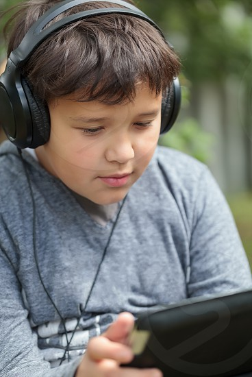 Teenager in earphones outdoor listening to music or watching video on tablet PC photo