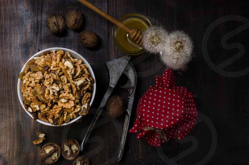 Walnuts in bowl with household goods on dark background photo
