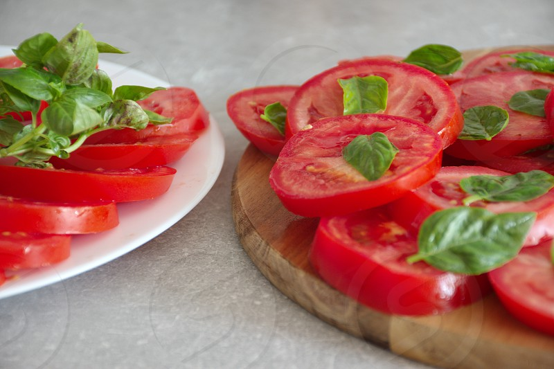 Closeup shot of the sliced tomato with basil on a plate and cutting board photo