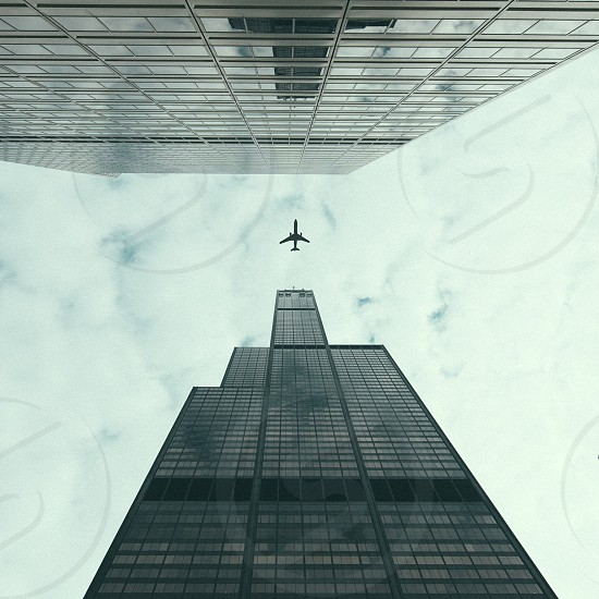 2 high rise building and a plane passed by above low angle photography photo